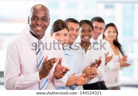 Successful business team applauding at the office - stock photo