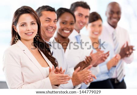 Successful business team applauding at the office looking happy - stock photo