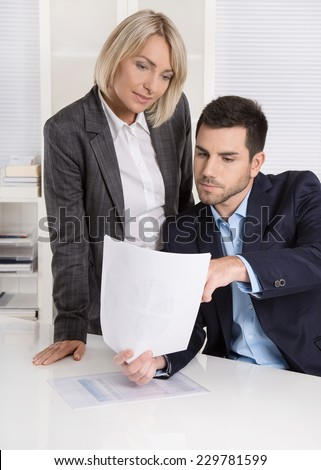 Successful business team: Female boss talking with her colleague about the finance report.