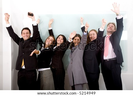 successful business team in an office looking happy with arms up