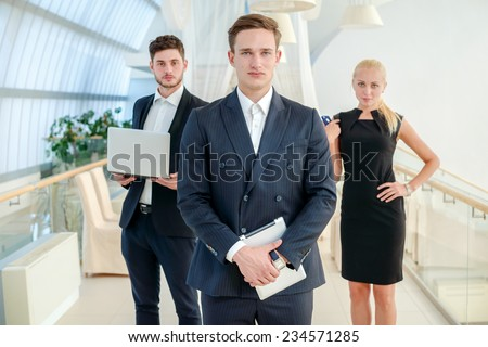Successful business team leader. Confident businessman holding his tablet and looking at the front while his colleague businessmen holding a laptop in the background - stock photo