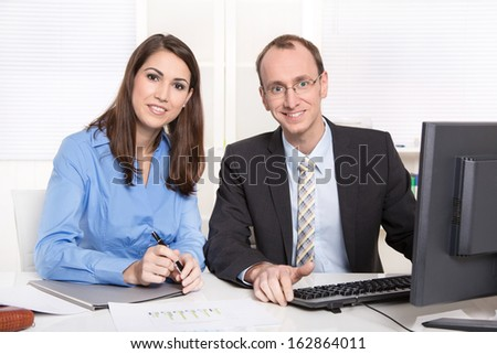 Successful business team - man and woman facing at camera - sitting at desk with computer. He is wearing tie and suit - she a blue blouse. - stock photo