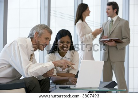 Successful business team of four with two on laptop - stock photo