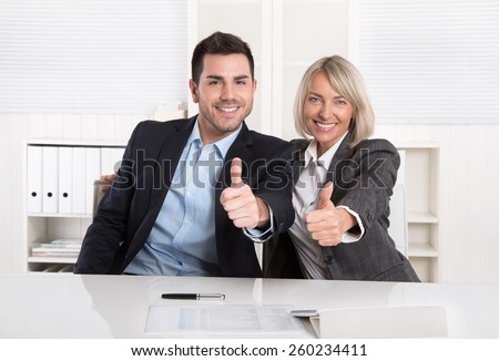 Successful business team or happy businesspeople making recommendation gesture. - stock photo