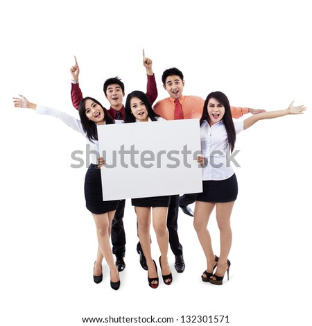 Successful business team raised hands holding blank billboard