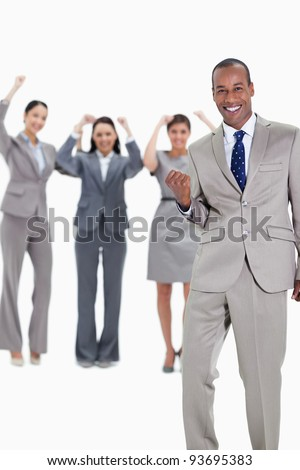 Successful business team with a happy businessman in foreground and three enthusiastic co-workers raising their arms - stock photo