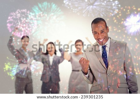 Successful business team with a man in the foreground against colourful fireworks exploding on black background - stock photo