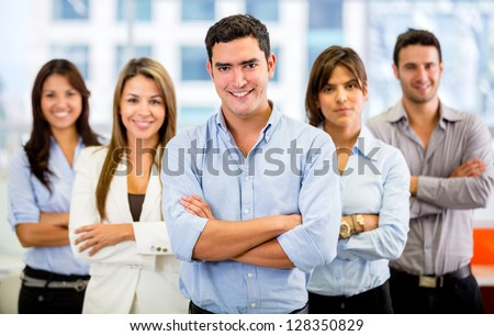 Successful business team with arms crossed at the office - stock photo