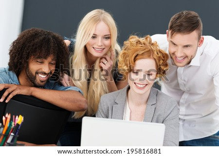 Successful business team with happy smiles grouped together around a laptop computer having a planning and strategy meeting - stock photo