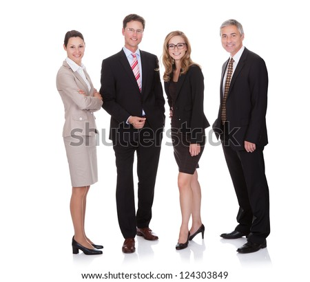 Successful business team with two attractive businesswoman and two middle-aged businessmen standing in a row smiling at the camera - stock photo