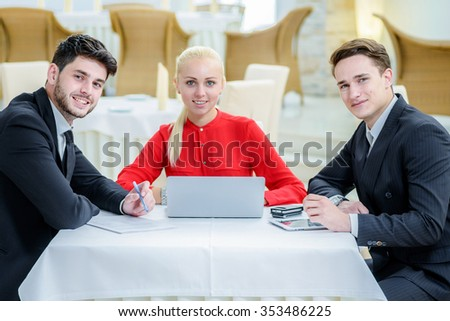successful business. Three successful people sitting at the table and smiling directly at the camera