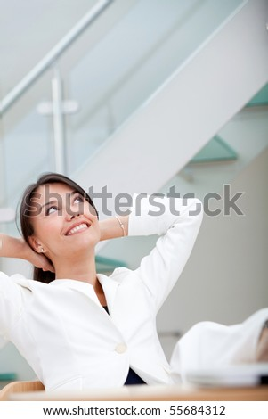 Successful business woman at the office with her feet on the desk - stock photo