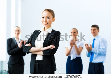 successful business woman in the office, around applauding colleagues - stock photo