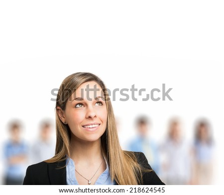 Successful business woman looking up with her staff in background at office - stock photo