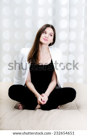Successful business woman on the sofa with her feet thinking - stock photo