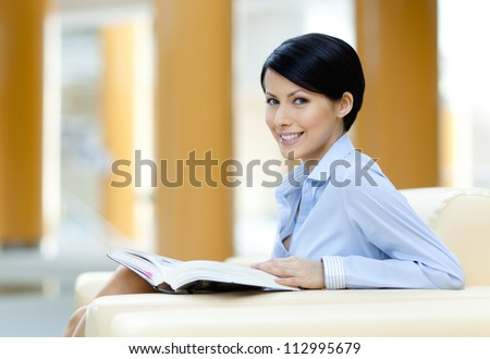 Successful business woman rests at the sofa reading book at the hall - stock photo