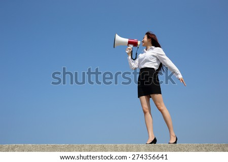 Successful business woman shouting in megaphone with blue sky background, full length, asian - stock photo