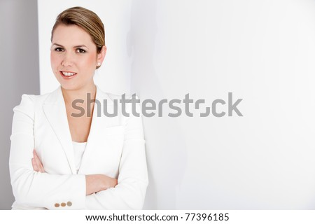 Successful business woman with arms crossed at the office - stock photo