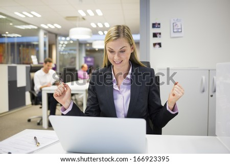 Successful business woman with arms up at the office - stock photo