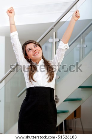 Successful business woman with arms up at the office