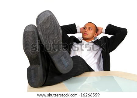 Successful Businessman A young satisfied businessman sitting by desk at office feet on table thinking.