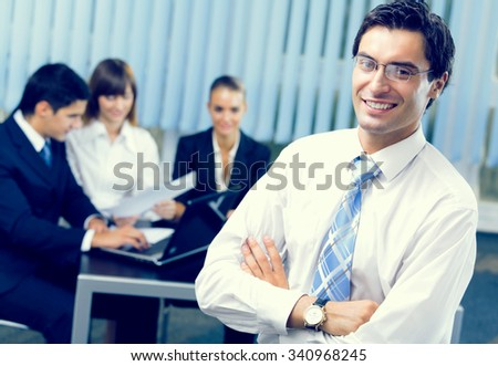 Successful businessman and businessteam at office meeting - stock photo