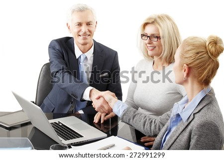Successful businessman and businesswomen sitting in front of laptop at the table and shaking hands. Group of business people sitting at business session. Isolated on white background. - stock photo
