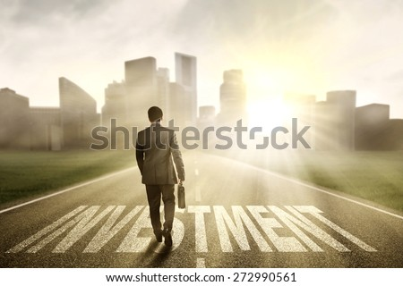 Successful businessman carrying a briefcase and walk on the road with an investment text - stock photo