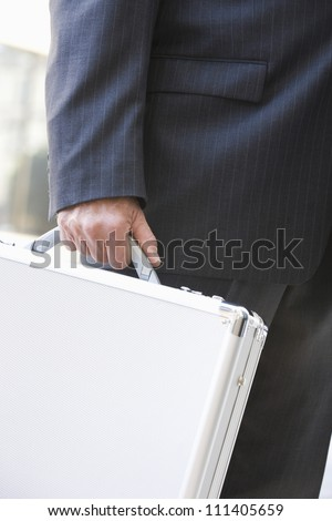 Successful businessman carrying briefcase - stock photo