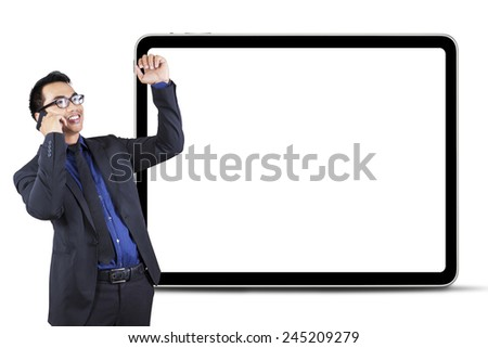 Successful businessman celebrate his success while listening good news from the phone in front of a blank board - stock photo