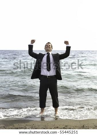 successful businessman celebrating on beach - stock photo