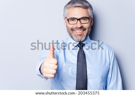 Successful businessman. Cheerful mature man in shirt and tie looking at camera and showing his thumb up while standing against grey background - stock photo