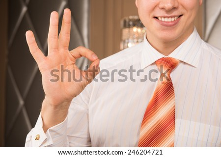 Successful businessman. Cropped image of cheerful young man in formalwear gesturing and smiling   - stock photo