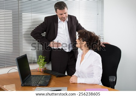 Successful businessman explaining something to his pretty colleague while they looking at monitor - stock photo