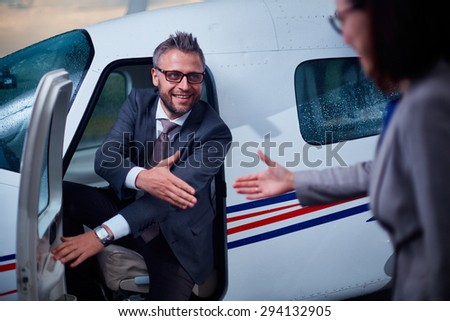 Successful businessman giving hand to his colleague while sitting in airplane  - stock photo