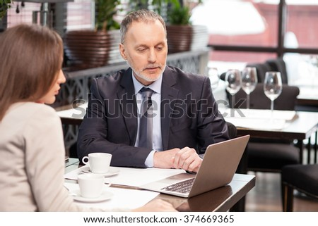 Successful businessman has a business lunch with his colleague in cafe. They are sitting at the table and looking at the laptop with seriousness. The man and woman are drinking coffee - stock photo