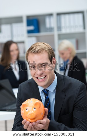 Successful businessman holding a piggy bank cupped in his hands as a measure of his achievements and responsible attitude to saving for retirement or towards a goal - stock photo