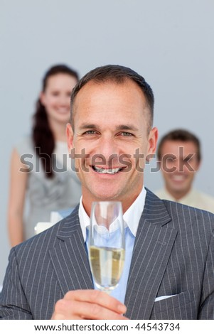 Successful businessman holding Champagne with his team in the background - stock photo