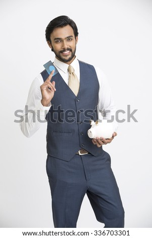 Successful businessman holding credit card with piggy bank on white background. - stock photo