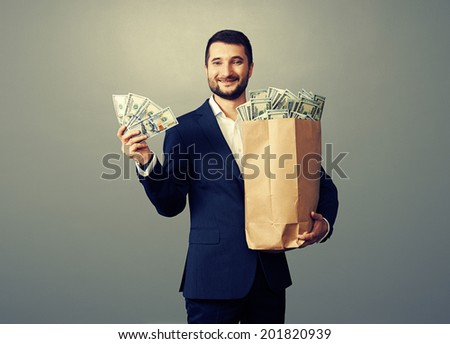 successful businessman holding paper bag with money and smiling. studio photo over grey background - stock photo