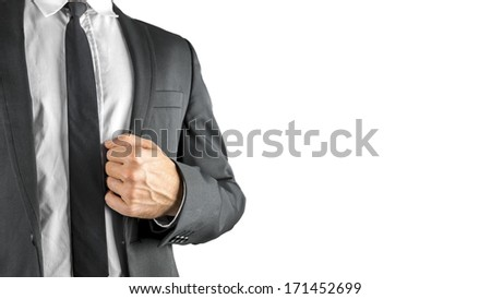 Successful businessman holding the lapel of his suit jacket in his hand conceptual of achievement on confidence, close up view of his chest and hand isolated on white with copyspace - stock photo
