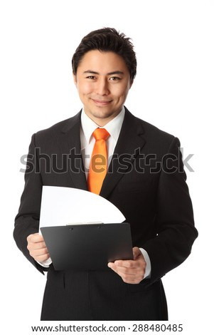 Successful businessman in a suit and tie holding a clipboard with a smile on his face. White background.