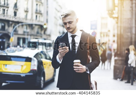 Successful businessman in black suit and using smartphone while going to his office at urban street with coffee, professional male banker searching information in internet on cellphone outdoors - stock photo
