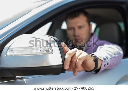 Successful businessman is sitting at the steering wheel of his car. He is adjusting side mirror with seriousness. Focus on mirror