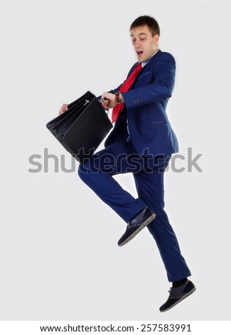 Successful businessman looking at his watch. In his hand is holding portfoliol. Hurry up and jumped - stock photo