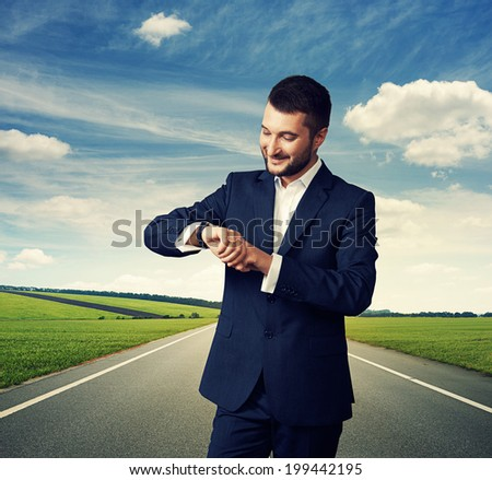 successful businessman looking at his watch over road