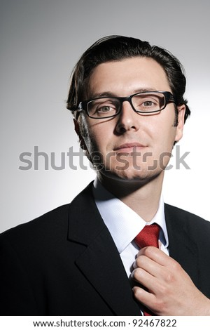 Successful businessman makes adjustments to his tie before meeting a client