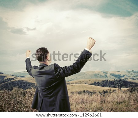 successful businessman on background of nature - stock photo
