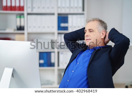 Successful businessman or corporate executive relaxing at his desk in the office with his hands clasped behind his head and eyes closed - stock photo