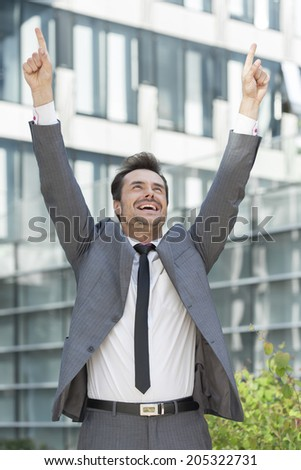 Successful businessman pointing upwards outside office building - stock photo